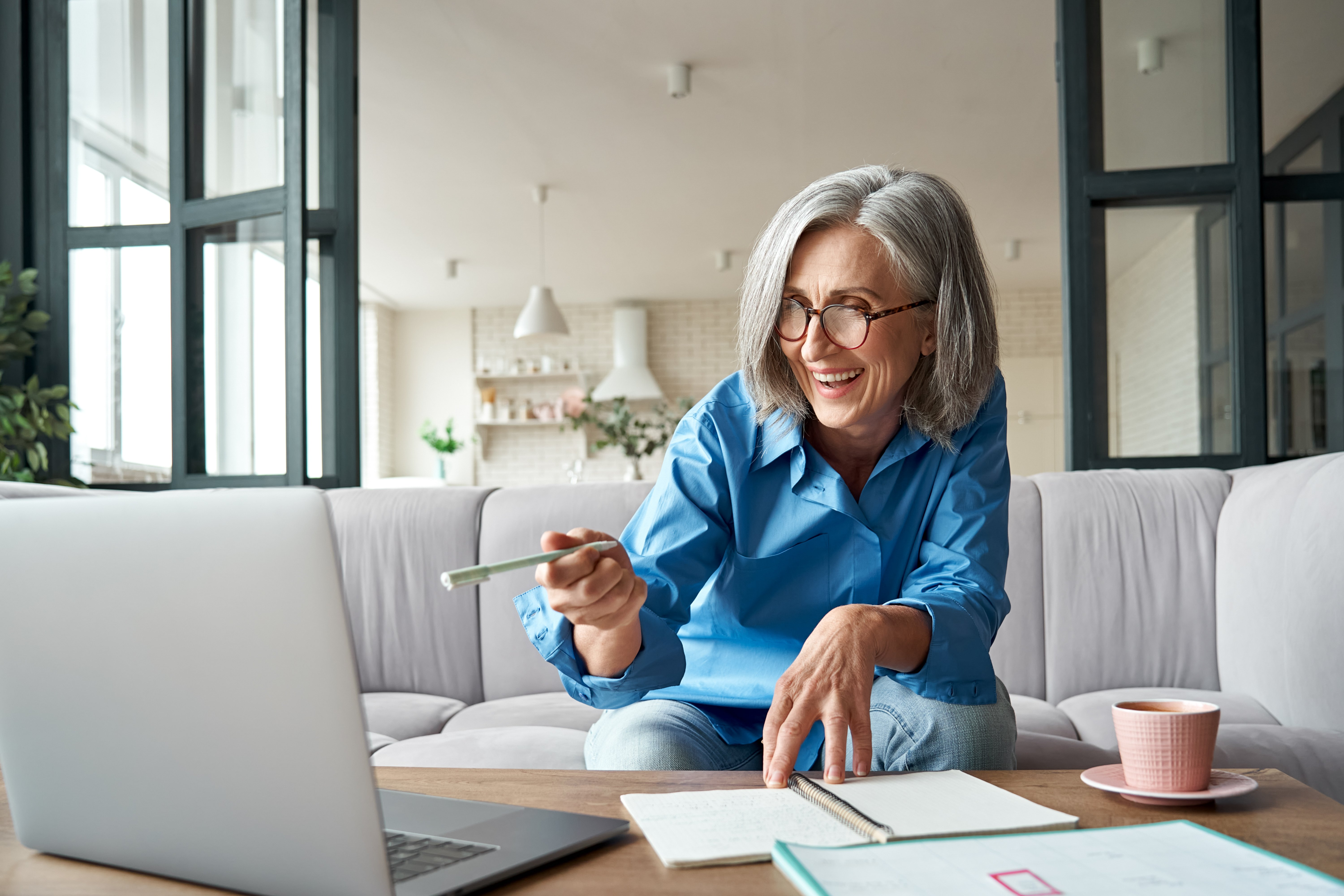 Older woman having a working lunch with coworkers over video chat