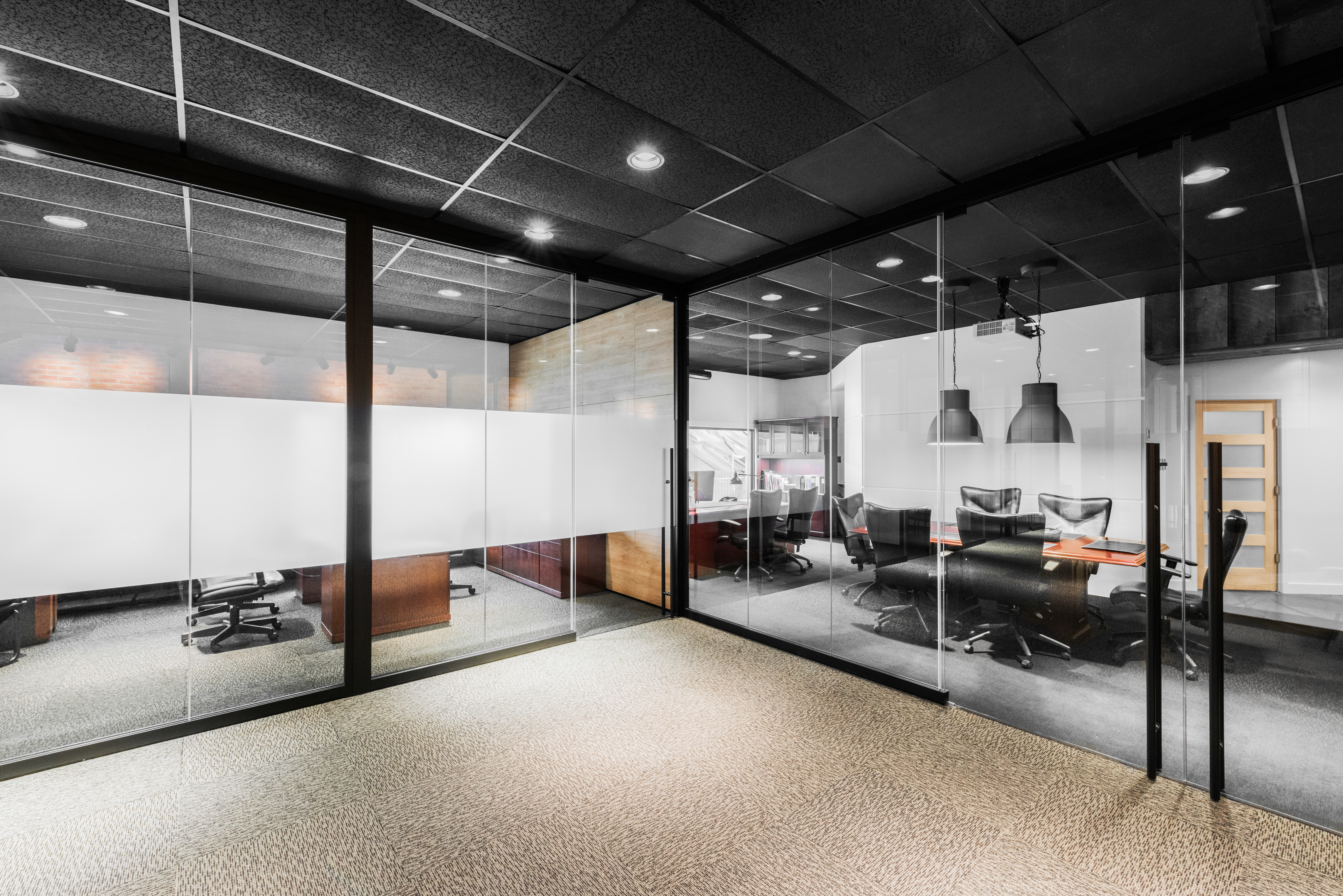 An office layout featuring sound-proof, demountable interior glass walls with black trim